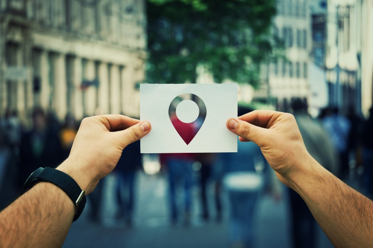Close up of man hands holding a white paper sheet with a pointer icon inside. GPS  searching for someone on a crowded city street. Travel navigation and planning location route.