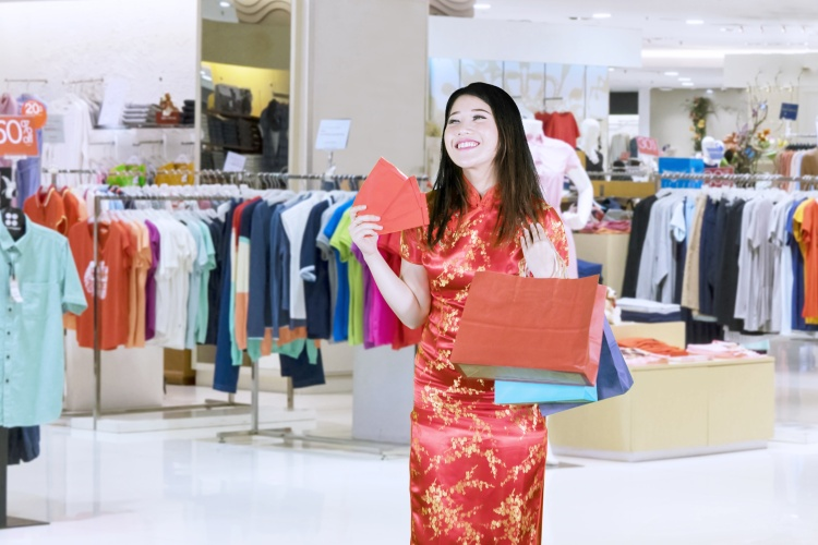 Beautiful Asian woman wearing cheongsam while carrying angpaos and shopping bags with a smile in a mall